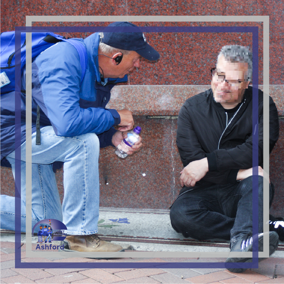 Photo: street pastor kneeling, passing someone sitting on the floor a bottle of water